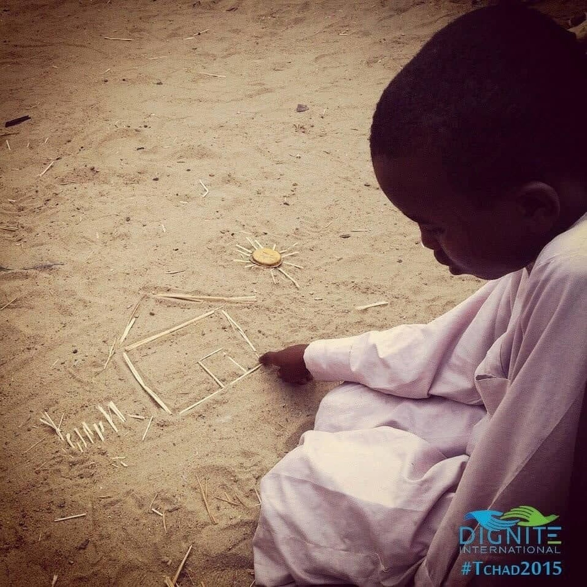 Enfant africain qui dessine une maison sur le sable apportons lui une aide humanitaire au Tchad