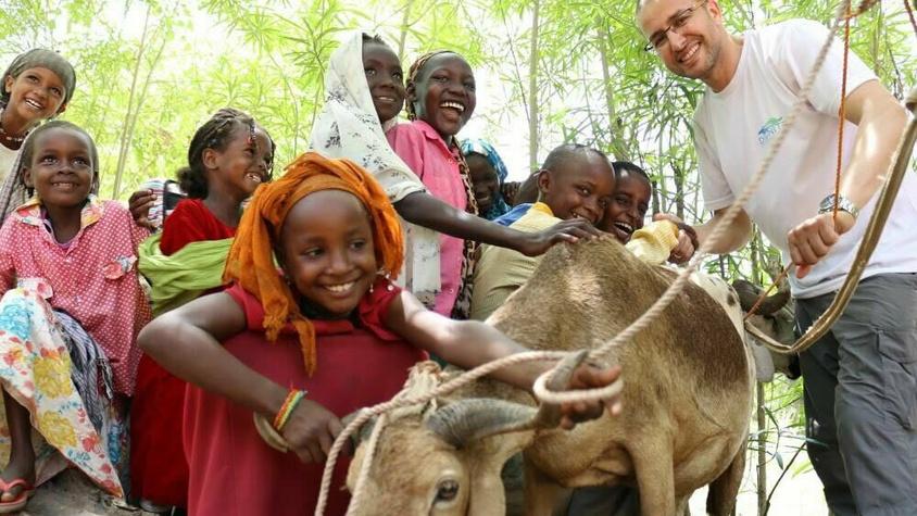 Enfants africains avec un bélier et un humanitaire de l'ong d'Afrique Dignité international souriants