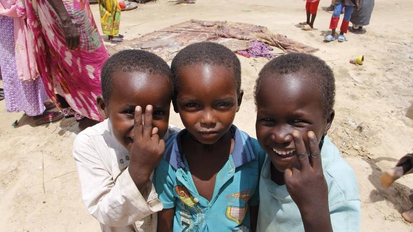 Enfants tchadiens centrafricains faisant le V de la victoire et qui sourient pour votre aide et don humanitaire